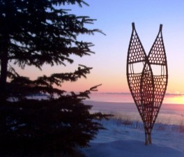 traditional snowshoes in front of a sunset