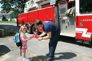 East Elementary School kindergartner Eliana Knapp, 5, accepts her 'helmet' from Torrington firefighter Mark Garrison as she prepares to board the fire department ladder truck for a ride to her first day of school Tuesday. Knapp won the honor in a drawing co-sponsored by the school district and the Torrington Early Childhood Collaborative. Jim Moore / Republican-American