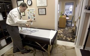 Dr. Shawn Carney of Northeast Natural Medicine get some equipment ready for a patient in his office in Newtown Wednesday. Steven Valenti Republican-American