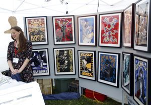 Amy Smith shows off artwork by Goshen artist Steven Sonklin during the 16th annual Litchfield Jazz Festival Friday night at the Kent School. The festival will run through Sunday. Christopher Massa Republican-American