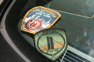 World Trade Center survivor Raymond J. Rosa has placed these patches in the rear window of his car. Jim Moore Republican-American.