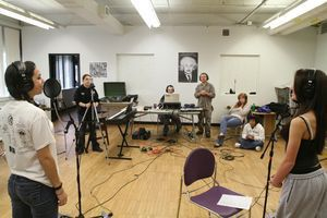 Torrington High School sophomores Jordyn Fenwick, far right, and Felice Magistrali, far left, record Wednesday in a music studio improvised by Music in Common founder Todd Mack, background, standing at right. A dozen high school students have collaborated to write and perform original music, and will take the stage Friday. Jim Moore Republican-American.