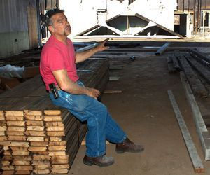 Carl Begley, owner of C&D Services in Wolcott, sits on a pile of fir rafters and points to king post trusses that were once part of the old Matthews & Willard Manufacturing Co. on Cherry Avenue in Waterbury. The wood and trusses will be recycled to be used in a barn and a cabin in New Hampshire.  cutline attribution name:Darlene Douty   Republican-American