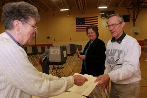 Gloria Gabelmann, left, a ballot clerk at Winsted's Pearson Middle School, distributes voting forms to Sandra and Ted Sweeney on Election Day in November 2011. Democrats and Republicans across Connecticut will cast ballots in primary elections today. RA Archive