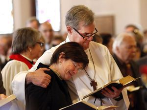 The Rev. Jack Gilpin, of Roxbury, hugs his wife Annie during his ordination Dec. 15 at St John's Episcopal Church in New Milford. Gilpin has appeared on stage and in television shows and movies over the past 30 years. Christopher Massa Republican-American