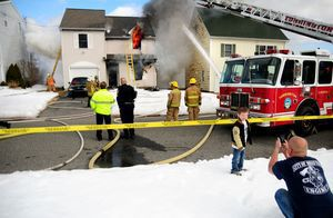 A boy has his photo taken in front of a burning home at 64 Griswold St. in Torrington on Monday afternoon. Alec Johnson/RA