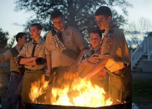 PLYMOUTH- 111013JS01- Joseph Guinazzo, 17, right, a member of Boy Scout Troop 21, places American flags into the fire on Sunday as part of a flag retirement ceremony he organized for his Eagle Scout project. Giunazzo and fellow scouts collected nearly 4000 retired flags.  Jim Shannon Republican-American