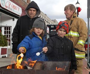Brothers M.J. and Jayden Butler roast marshmallows as Jim Brooke and Winsted volunteer firefighter Edward Harris look on during Main Street Christmas festivities in Winsted on Saturday afternoon.  Michael Kabelka/Republican-American