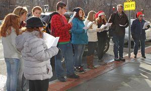 Gilbert School music teacher Adam Atkins leads students singing Christmas carols during Main Street Christmas festivities in Winsted on Saturday afternoon.  Michael Kabelka/Republican-American