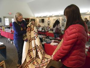 Jane Meigs, left, of Millerton, N.Y., and Monika McKillen of Warren have their eyes on a handmade quilt at the Trinity Lime Rock Church Fair Saturday. Ruth Epstein Republican-American