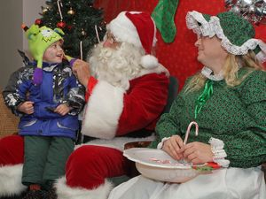 Maximilliano Nieves talks to Santa and Mrs. Claus during Main Street Christmas festivities in Winsted on Saturday afternoon. More than 100 toured the sidewalk along Main Street to enjoy horse-drawn hay rides, the roasting of marshmallows with local firefighters, pictures with Santa and the Christmas Tree lighting at East End Park. The event will also included hot chocolate, popcorn, cookies, carol singing, crafts and storytelling. Tricia Twomey, director of the parks and recreation department, said that this was the fifth year for the festival sponsored by Friends of Main Street and was supported by various local businesses. Michael Kabelka/Republican-American