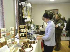 Julianna Kreta adjusts some of the crystal sun catchers she was selling the United Church of Christ Church Holiday Fair in Cornwall Saturday. Also among her inventory was a collection of birthstones and her oil paintings of birds on greeting cards. Ruth Epstein Republican-American