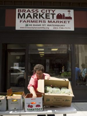 Sue Pronovost puts fresh vegetables in boxes outside of the Brass City Harvest headquarters along Bank Street in downtown Waterbury Thursday. Her nonprofit organization puts fresh produce into the hands of several thousands of people in the Greater Waterbury area. Erin Covey Republican-American.
