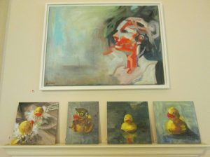 Katie Ré Scheidt's self- portrait, top, and a series of rubber ducky paintings on display at Gunn Memorial Library in Washington. Destiny Lopez / Republican-American
