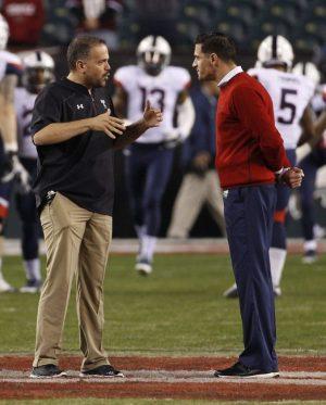 Temple head coach Matt Rhule, left, talks with Connecticut head coach Bob Diaco, right, during warm-ups prior to the first half of an NCAA college football game, Saturday, Nov. 28, 2015, in Philadelphia. (AP Photo/Chris Szagola)