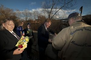 Members of the Waterbury Veterans Memorial Committee, from left, Glora Potter, Bob Dorr and Dan Potter prepare to lower a boat of flowers into the Naugatuck River in Waterbury on Monday during a Pearl Harbor memorial ceremony on the Pearl Harbor Memorial Bridge.  Jim Shannon Republican-American