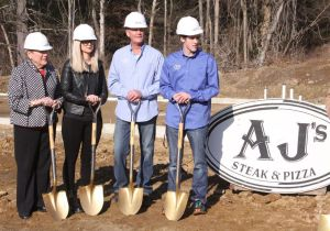 Mark Wasdo, second from right, owner of AJ's Steak and Pizza in Goshen, is flanked on Thursday by his son, Josh, and daughter, Alicia, as well as JoAnn Ryan, president and CEO of the Northwest Connecticut Chamber of Commerce, during a groundbreaking ceremony at the site on Route 4 where a new AJ's is being built. John McKenna Republican-American