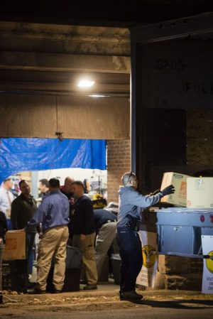 A team of Waterbury police investigators loads up a trailer Thursday night with items found at 1694 North Main Street. Erin Covey Republican-American