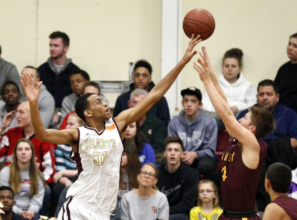Waterbury, CT- 14 March 2016-031416CM07-  Sacred Heart's John Riddick blocks the shot of Granby's Ray Mooney during their Class M quarterfinal matchup in Waterbury on Monday.  The Hearts would go onto win, 93-36.    Christopher Massa Republican-American