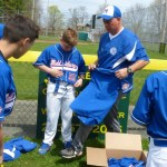 Eric Fauth hands out uniforms to the 12 year-old competition team players at Middlebury Baseball's opening day on Saturday. (Palladino/RA)