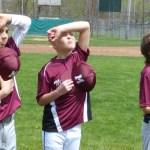 Middlebury Baseball players honor the flag on a sun-splashed opening day Saturday. (Palladino/RA)
