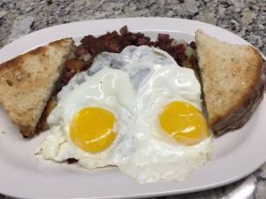 Homemade corned beef hash is flanked by eggs sunny-side up and Italian bread toast at Big Guys Diner in Wolcott.