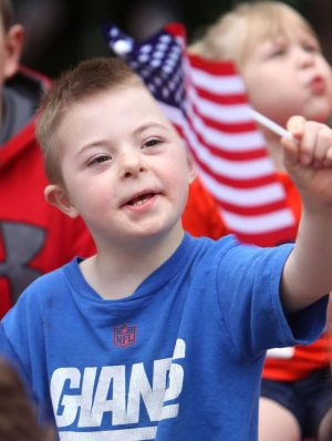 Collin Northrup, 7, of Naugatuck waves his flag to marchers during the Memorial Day parade in Naugatuck on Monday. Steven Valenti Republican-American