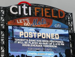 A large video screen announces that Monday's baseball game between the New York Mets and the St. Louis Cardinals has been postponed due to rainning, Monday, July 25, 2016, in New York. The game will be played as part of a doubleheader Tuesday. (AP Photo/Kathy Willens)