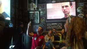 Joe Moravsky takes a picture of himself, on the TV screen above and behind him, in the American Ninja Warrior finale, while inside a crowded room of friends and family in 1st and 10 Sports Bar & Grill in New Milford on Monday night.