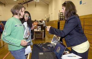 From left, Angel Blauvelt, 12, and Anna Zavala, 12, listen to Dawn Mazini-Gutowski, president of JB Industries, Inc. during the Northwest Chamber Manufacturing Expo at Torrington Middle School in Torrington Friday. This expo-style event gave students an opportunity to meet local manufacturers, learn about careers in manufacturing, and participate in fun, hands-on activities.  Steven Valenti Republican-American