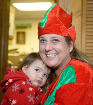 Jenna Nanni, 1, of Winsted hangs out with her mom, Lisa Nanni, dressed as an elf, while selling Christmas cookies during the First Church of Winsted´s 94th annual Christmas Fair in Winsted Saturday. Steven Valenti Republican-American