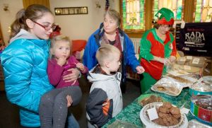 From left, Alyssa Cohen, 1,2 her sister Abby Cohen, 3, and her brother Devin Cohen, 7, all of Southington help their grandma Kathy Garneau of Winsted pick out cookies during the First Church of Winsted´s 94th annual Christmas Fair in Winsted Saturday. Steven Valenti Republican-American
