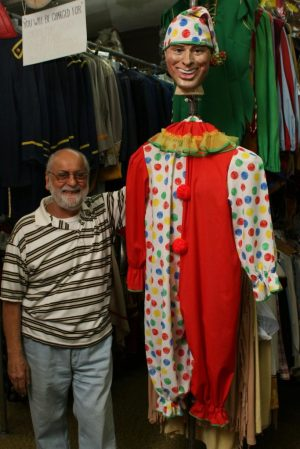 Michael Rinaldi, owner of Arabesque Dance and Costume on Bank Street in Waterbury, poses next to a clown costume at his store Wednesday. Laraine Weschler Republican-American