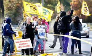 Workers join a picket line in front of Rosegarden Health & Rehab Center on East Main Street in Waterbury Tuesday.  Steven Valenti Republican-American