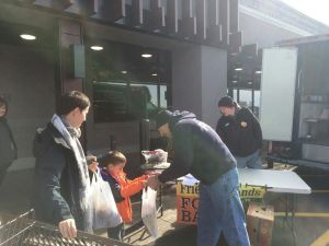 Torrington police Detective Todd Fador accepts a bag of donations from Samuel Gooden, 5, of New Hartford, and his mother, Leah, for the police union's food drive on Saturday outside Market 32 in Torrington to support the Friendly Hands Food Bank. Bruno Matarazzo Jr. Republican-American