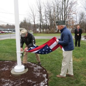 Ruth Epstein Republican-American  Robert J. Loucks, left, and John F. Perotti raise the flag on the new flagpole on the lawn at the Salisbury Bank and Trust Co. Wednesday.