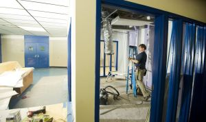 Dane Lilly, and electrician with John L Simpson & Co Inc, of Bridgeport, works on lighting inside one of the new offices as construction continues Wednesday at Crosby High School in Waterbury. Jim Shannon Republican-American