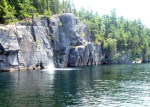 Splash! Kids and rocky cliffs with deep water below is a recipe for fun on a warm summer day. (Tim Jones/EasternSlopes.com photo)