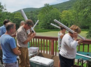 Kent Land Trust Land Manager Mike Benjamin checks out the sun through one of the pinhole viewer tubes he helped design during a Solar Eclipse Party Monday afternoon at the groupþÄôs headquarters as Josh Fields of Greenwich looks on. Kristin Strid and Susan Strid, right, of South Kent were among the first to create one. Lynn Mellis Worthington Republican-American