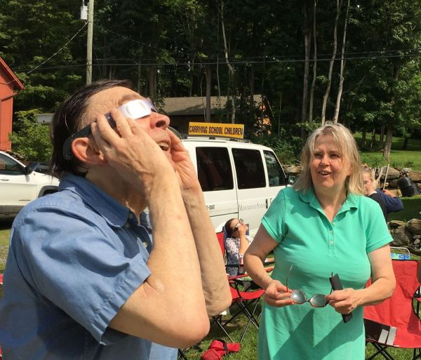 Many people shared solar eclipse glasses and Walter Schwarz of Sharon enjoyed taking a look as his wife, Linda Swenson looked on during Monday's Solar Eclipse Party at the Kent Land Trust. Lynn Mellis Worthington Republican-American