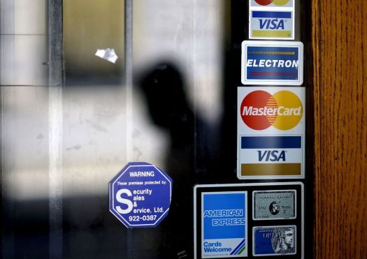 FILE - In this July 18, 2012, file photo, a pedestrian walks past credit card logos posted on a downtown storefront in Atlanta. On Monday, Sept. 11, 2017, Equifax said it has made changes to address customer complaints since it disclosed a week earlier that it exposed vital data on about 143 million Americans. Equifax has come under fire from members of Congress, state attorneys general, and people who are getting conflicting answers about whether their information was stolen. Equifax is trying again to clarify language about peopleþÄôs right to sue, and said Monday it has made changes to address customer complaints. (AP Photo/David Goldman, File)