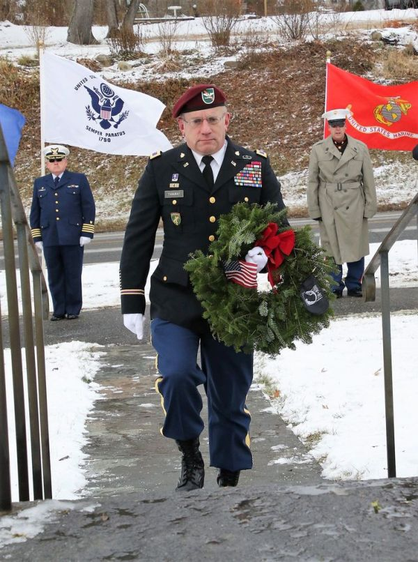 Col. Mark Yanaway (Ret.), Army veteran and commander of American Legion Post 27 in Litchfield, carries a wreath to the All Wars Memorial in Bantam during the Wreaths Across America ceremony on Saturday. Yanaway placed the wreath in honor of the 93,129 U.S. service members whose last-known status was prisoner of war or missing in action. John McKenna Republican-American