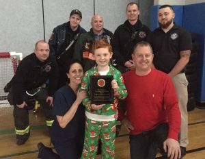 Nathan Gryniuk stands with his parents and Torrington firefighters Brian Parks, Tim O'Donnell, Lt. Jay Dixon, Scott Rodgers and LCD dispatcher George Norton on Friday after they surprised him with a plaque. The plaque was to recognize him for providing help and information to assist dispatchers and firefighters when they responded for a medical aid call in October for his mother when she became ill and unable to speak. Contributed