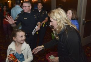 Campership Director Sandy Monteiro; thanks a young lady after she donated to the Greater Waterbury Campership Fund during intermission at the Palace Theatre in Waterbury on Sunday. Among the volunteers who participated were Waterbury police officers Chris Gagnon and Chris Gagnon, background, as well as Campership Director Joyce DeCesare, right. Jim Shannon Republican-American