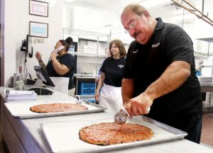 Steven Valenti Republican-American Gary Bimonte, Frank Pepe's grandson, cuts a ceremonial pizza as the newest Frank Pepe's pizza at 160 Reidville Drive in Waterbury opened in April.