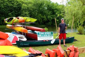 Eric Davis of Goshen, a Clarke Outdoors employee at their New Milford location, shows off the rental company's fleet of kayaks, canoes and standup paddle boards. Alicia Sakal/ Republican-American