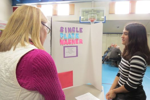 Student Maryann Palmer explains her Single Plate Washer project to judge Theresa Graney during last week's Invention Convention at Lee H. Kellogg School in Falls Village. Ruth Epstein Republican-American