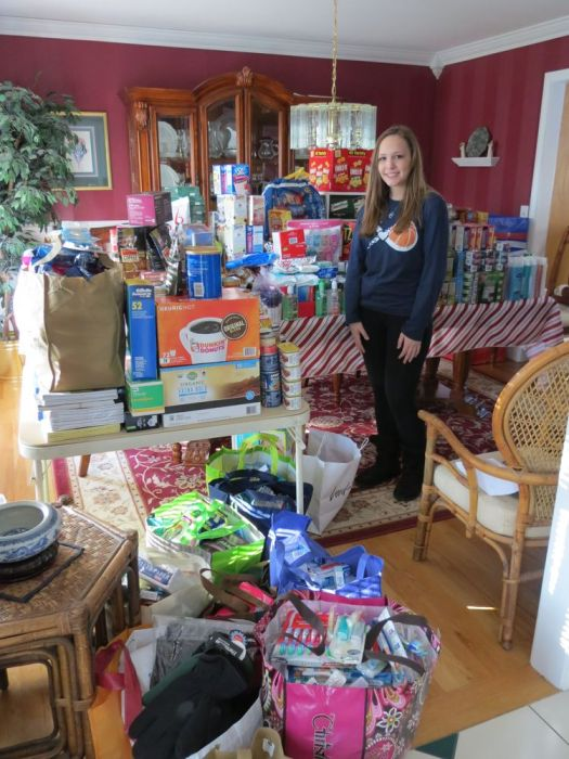 Contributed  Kelly Shpak, 16, a junior at Oxford High School, stands in her family's dining room last year with collections for care packages to send to the troops overseas. Shpak is at it again this year, collecting supplies and postage for A Project from the Heart.