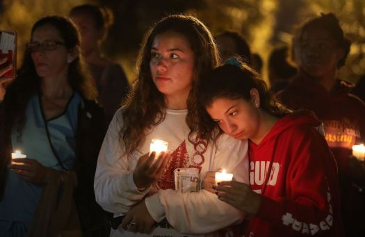 Chloe Leffler, 14, left, of Coral Springs, Fla., and Dominique Cornwall, 15, of Parkland, attend a statewide vigil to honor the victims of the Douglas High School shooting at Betti Stradling Park in Coral Springs on Feb. 19. TNS
