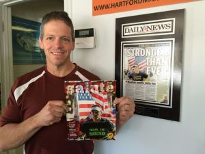 Avid runner Doug Benedetto, a member of the Torrington Board of Public Safety, poses with a copy of Salute, the official program of the Marine Corps Marathon, that has a picture of him running the marathon in 2013. Bruno Matarazzo Jr. Republican-American